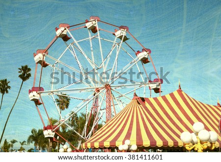 aged and worn vintage photo of ferris wheel with palm trees                               - stock photo