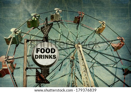 aged and worn vintage photo of food and drinks sign at carnival with ferris wheel - stock photo