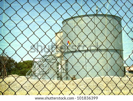 aged and worn vintage photo of  industrial oil tanks behind fence