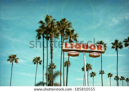 aged and worn vintage photo of liquor and groceries store sign with palm trees - stock photo