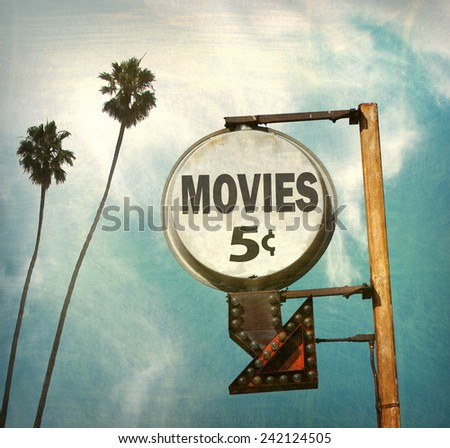 aged and worn vintage photo of movies sign with palm trees - stock photo