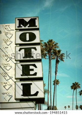 aged and worn vintage photo of neon motel sign and palm trees - stock photo