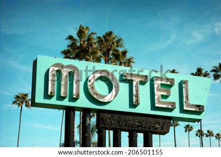 aged and worn vintage photo of old neon motel sign with palm trees - stock photo