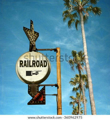 aged and worn vintage photo of railroad sign with palm trees - stock photo