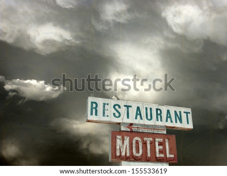 aged and worn vintage photo of restaurant sign and storm clouds                             - stock photo