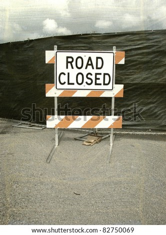aged and worn vintage photo of road closed sign with cloudy sky - stock photo