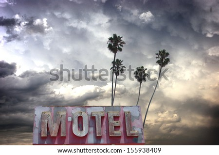 aged and worn vintage photo of stormy sky with palm trees and neon motel sign - stock photo