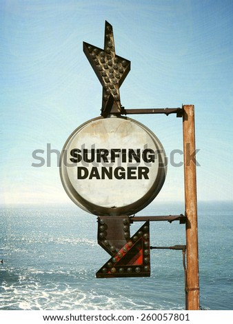 aged and worn vintage photo of surfing danger sign on beach - stock photo