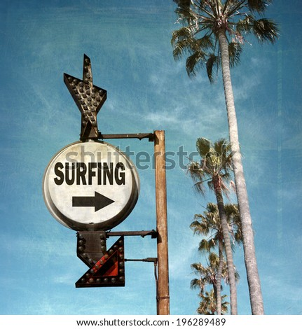 aged and worn vintage photo of surfing sign with arrow                            - stock photo