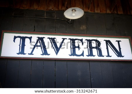 aged and worn vintage photo of tavern sign with light                                - stock photo