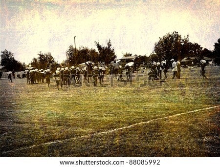 aged and worn vintage photo of unidentifiable young american football players on field - stock photo