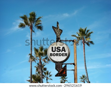 aged and worn vintage photo of usa border sign with palm trees                                - stock photo
