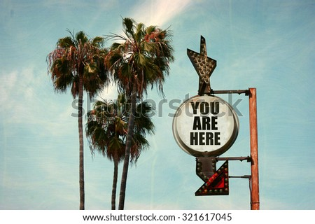 aged and worn vintage photo of you are here sign with palm trees