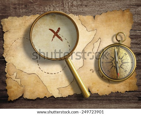 aged antique nautical compass and magnifying glass on table with treasure map - stock photo