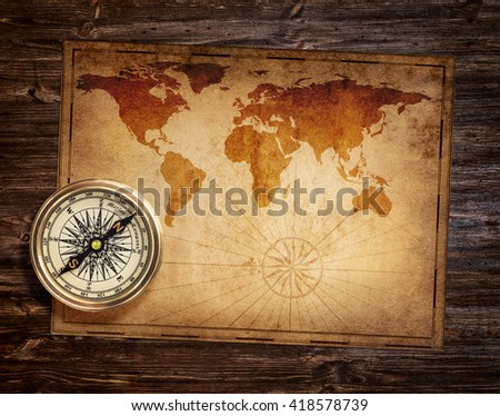 aged antique nautical compass and old treasure map - stock photo