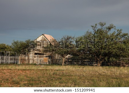 Aged barn, built of wooden boards, leaning near disused corrals/Weathered Old Wooden Barn Leans with Age at Disused Ranch Fences in Summertime/Vintage wooden little Barn and summer vegetation - stock photo