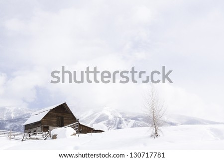 Aged barn on snowy hillside with ski lifts and ski slopes in background. - stock photo