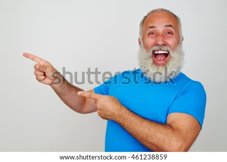 Aged bearded male is gesturing happiness and pointing with fingers to his right side on white background