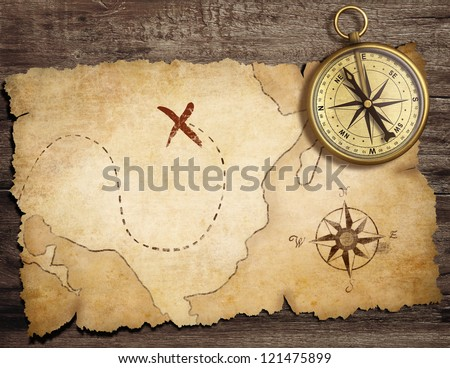 aged brass antique nautical compass on table with old treasure map - stock photo