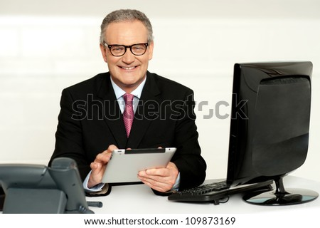 Aged businessman in glasses using tablet sitting in office - stock photo