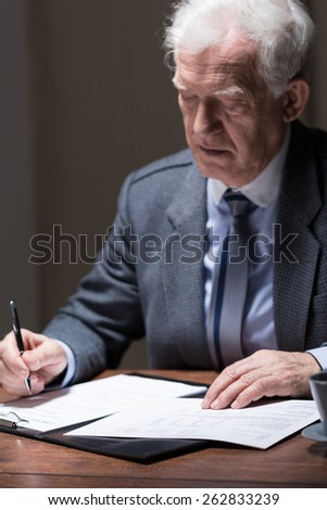 Aged businessman sitting at the desk and doing paperwork - stock photo