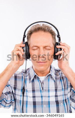 Aged calm hipster with headphones listening to music