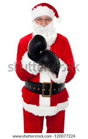 Aged cheerful Santa wearing boxing gloves, getting ready for the competition.
