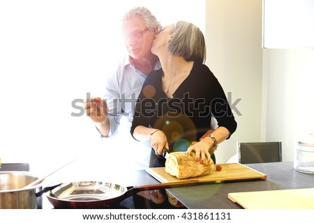 Aged couple cooking and eating in the kitchen - stock photo