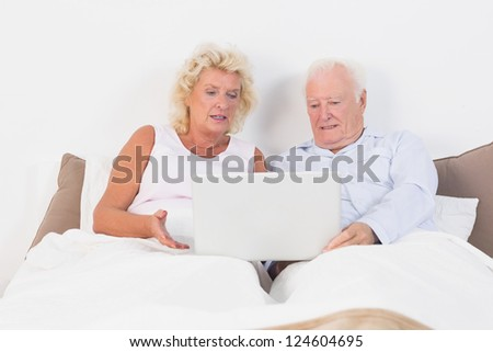 Aged couple reading or using a tablet on the bed - stock photo