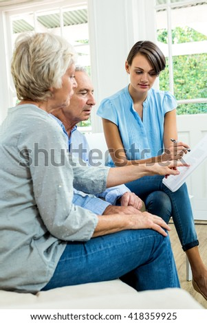 Aged couple reading report with female consultant at home - stock photo