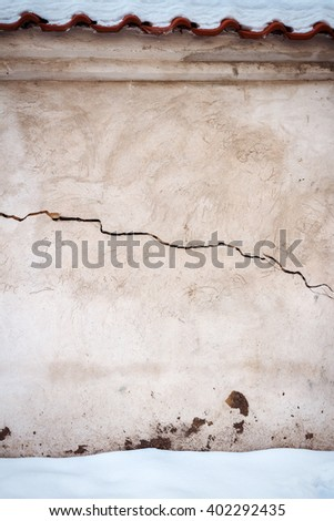 Aged cracked white plaster street wall and ground covered with snow - stock photo