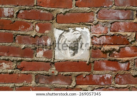 Aged crumbling street wall background with red bricks texture and gargoyle - stock photo