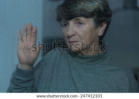 Aged depressed woman holding her hand on rainy glass - stock photo