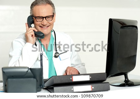 Aged doctor attending call in front of lcd screen smiling at camera - stock photo