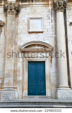 Aged door decorated with stone sculptures of a church inside old town of Dubrovnik, Croatia