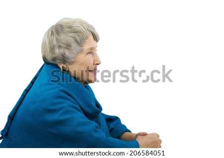 Aged gray-haired woman in blue poncho sitting in profile - stock photo