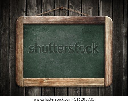 Aged green blackboard hanging on wooden wall as a background for your message - stock photo