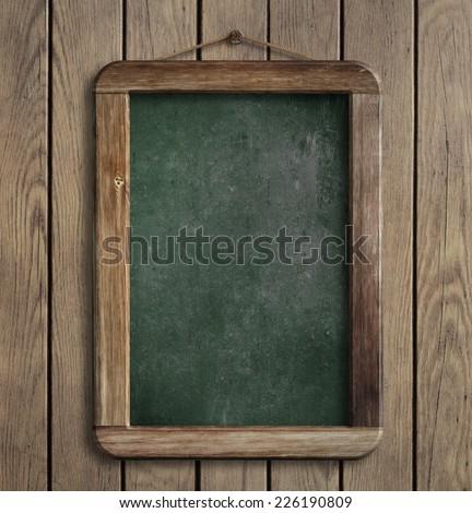 Aged green menu blackboard hanging on wooden wall - stock photo