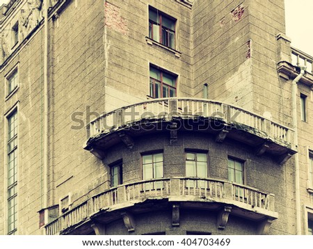 Aged half-ruined balcony on the building with peeling lining. Detailed view of architectural elements at the one of the old St.Petersburg buildings, Russia. Sepia filter  applied.  - stock photo