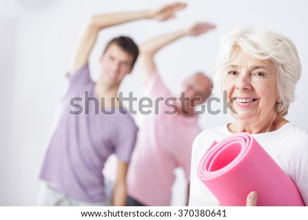 Aged happy woman with mat ready for fitness classes