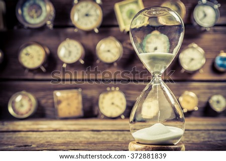 Aged hourglass on the background of clocks - stock photo