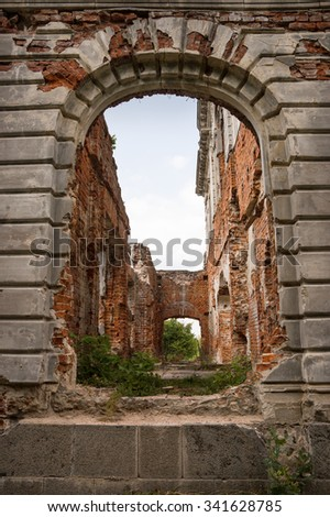 Aged luxury gloomy tunnel hole with large dark grey arc in deserted home of philanthropist Mikhail Tereshchenko destroyed by war. Zhytomyr, Ukraine, Europe. Front view with space for text on white sky - stock photo