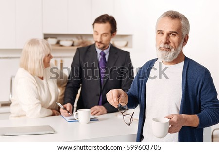 Aged man drinking tea while his wife signing the contact