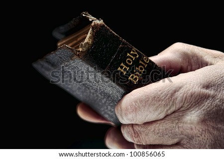 Aged man hands firmly holding and clinching an old and damaged antique Holy Bible Christian religious book during a religious prayer service in a protestant church - stock photo