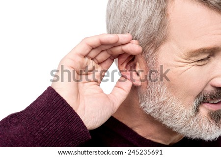 Aged man holds his hand near ear and listening - stock photo
