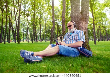Aged man in modern fashionable clothes is sitting under the tree in picturesque park and listening to music on his smart phone - stock photo