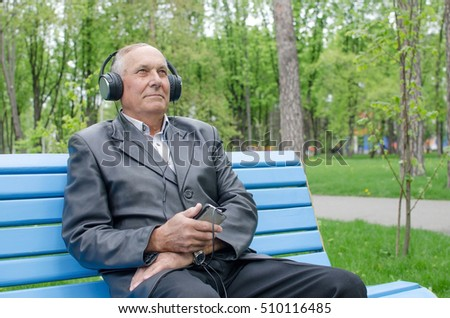 Aged man is listening to music in the park