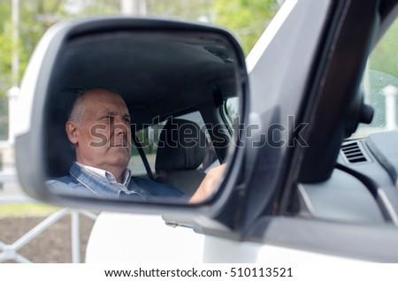 Aged man is sitting in the car