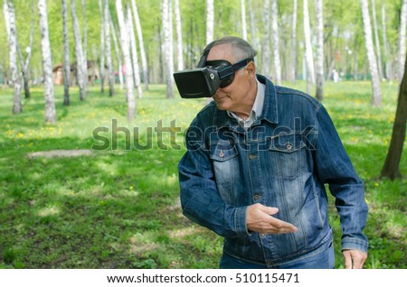 Aged man is using virtual glasses in the park