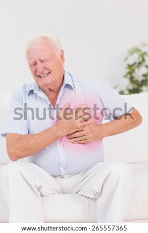 Aged man suffering with heart pain on a sofa - stock photo